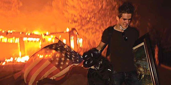 Man carrying American flag with burning house in background